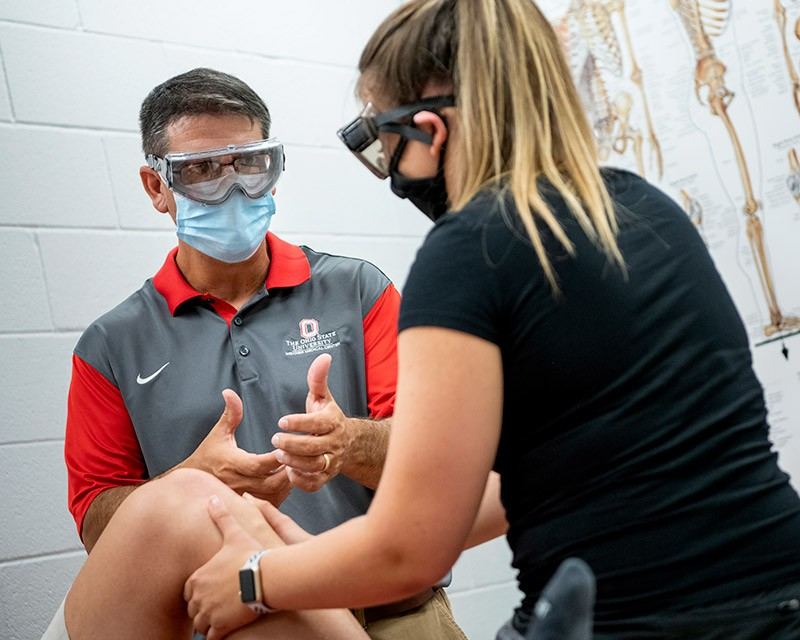 Medical faculty teaches student about physical therapy